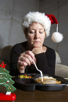 Unhappy woman wearing a christmas stocking hat eating a turkey TV dinner on a tray table in the basement